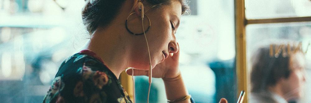 Bilde av kvinne som hører på lyd fra telefonen sin på kafé