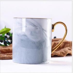 Keramisk kopp med marmormønster og gullhåndtak